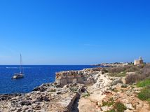 Scenic view of the coastline and cliffs in ciutadell menorca rocky cliffs over a bay with blue sea with boat and sunlit sky stock photography