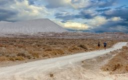 Tourists hiking under a sky with clouds. La Graciosa, Lanzarote, Canary Islands, Spain. royalty free stock photography