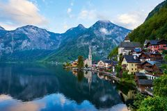 Scenic view of Hallstatter lake with a boat in Austrian Alps. Autumn sunset on Hallstatt lake with beautiful clouds and reflection stock photos