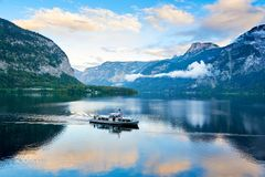 Scenic view of Hallstatter lake with a boat in Austrian Alps. Autumn sunset on Hallstatt lake with beautiful clouds and reflection stock images