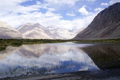 The scenic view of the Himalayan mountain range with reflection on a water body. Shot en-route to Nubra Valley from Leh Stock Images