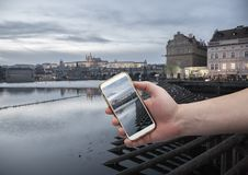 Scenic view of historical center Prague, Charles bridge and buildings of old town Hand with a smartphone, on the screen of which royalty free stock photos