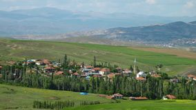 Scenic view of an Iranian village. Nestled in between green fields and valleys. Cypress trees border the village stock video footage
