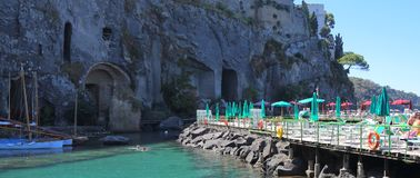 Italy Sorrento - the Amalfi coast. Scenic view of a jetty with sun shades set against a cliff on the Amalfi coast in Sorrento Italy Royalty Free Stock Image