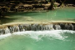 Scenic view on Kuang Si waterfall with turquoise water on a sunny day. Luangprabang, Laos Royalty Free Stock Images
