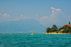 Scenic view of lago di Garda, Italy. Scenic view of lago di Garda - Garda Lake - with azure water, yellow buoy, blooming plants on the coast and alp mountains on Royalty Free Stock Image