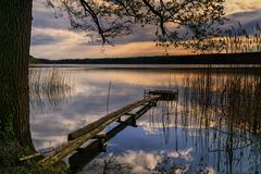 Scenic view of the lake at dusk in Brodnica Lake District, Poland, Europe. Sunset after a sunny spring day. A footbridge made of wooden logs with a platform Stock Image