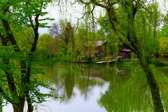 Lake and the wooden house through the trees. Scenic  view on the lake and the wooden house through the  trees stock photos