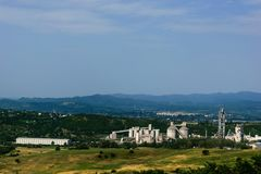 Scenic view of landscape with huge cement factory surrounded by green vegetation.  Stock Photography