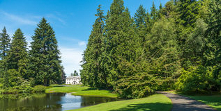 Scenic view of lawn and trees with reflection in the lagoon in b Stock Photo