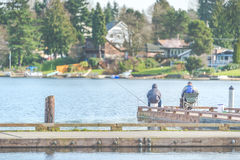 Scenic view of a man fishing on a pier in a big lake in the park. Stock Photos