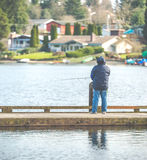 Scenic view of a man fishing on a pier in a big lake in the park. Royalty Free Stock Photos