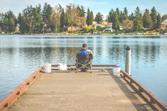 Scenic view of a man fishing on a pier in a big lake in the park. Royalty Free Stock Photography