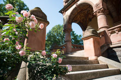 A scenic view of mansion arch, roses and stairs Stock Photo