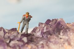 Scenic view of miniature figure in shape of a hiking person in the mountains and blue sky. Royalty Free Stock Photos