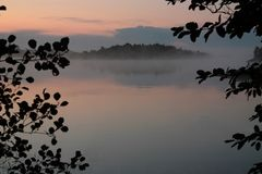 Scenic view of misty lake. Leaves silhouetted in foreground stock photo