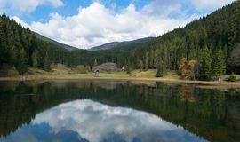 Scenic view of a mountain lake with the sky reflected in autumn. In northern Romania, Eastern Europe. Rural scene Stock Photo