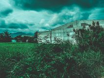 Mountain range view with old building. Scenic view of mountain range with field and old Royalty Free Stock Photo