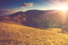 Scenic view of mountains with colorful hills at sunset. Filtered image:cross processed vintage and soft focus effect Stock Photo