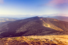 Scenic view of mountains with colorful hills at sunset. Filtered image:cross processed vintage and soft focus effect Royalty Free Stock Images