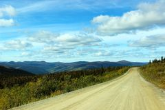 SCENIC VIEW OF MOUNTAINS FROM DIRT ROAD CLOUDS AND BLUE SKY. Scenic view of green Mountains from dirt road with bright blue sky and clouds. Taken in Alaska Stock Images