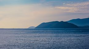 Scenic View of Mountains Near Ocean Royalty Free Stock Images