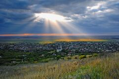 Free Scenic View Of A Village Light By Sun Through A Hole In The Clouds Royalty Free Stock Images - 181402529