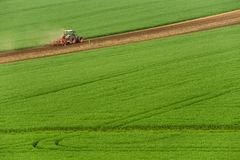 Scenic View Of Modern Farming Tractor Which Plowing Green Field. Agriculture Tractor Cultivating Wheat Field And Creating Green Ab Stock Images