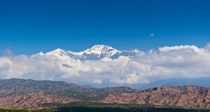 Free Scenic View Of Snow Capped Peak El Plata 6100 MSL Above The Clouds, As Seen From Lake Potrerillos, In Mendoza, Argentina Stock Photo - 215359450