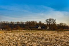 A field  with a view of 2 old barns with lots of trees. Royalty Free Stock Photo