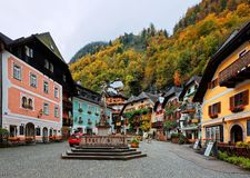 Scenic view of the old town square of Hallstatt, with a statue in the center, traditional colorful houses. Around the paved square, and fall mountains in stock image