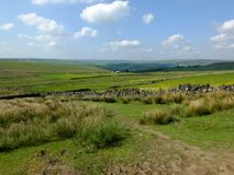 Scenic view of a path on the edge of moorland in calderdale west yorkshire with rough tussock grass with dry stone walls. Bordering pastureland with farmhouses stock photography