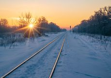 Scenic view of railway going far away at sunrise. Scenic view of railway going far away through winter field covered by fresh snowat sunrise royalty free stock photo