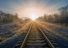 Scenic view of railway going straight ahead to rising sun. Scenic view of railway going straight ahead through winter field covered by frost to rising sun royalty free stock image
