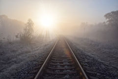 Scenic view of railway going straight ahead to rising sun. Scenic view of railway going straight ahead through winter field covered by frost to rising sun royalty free stock photography