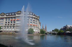 Scenic view of the river Ill - Strasbourg, France. The bank of the river Ill with fountain, palace and bridge. Strasbourg, France Stock Images