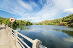 Scenic view of a road and lake in a mountain scenary. Stock Images