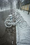 Bicycles smoothly covered with fresh snow after weather phenomen. Scenic view of a row of bicycles smoothly covered with fresh snow after weather phenomena Royalty Free Stock Photo