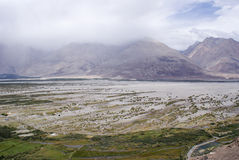 Scenic view of the sand dunes and greenery at Nubra Valley. Panoramic view of the landscape consisting of sand dunes and greenery at Nubra Valley, Leh Stock Image