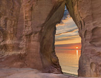 Scenic view through the sandstone arch at sunrise Stock Photos