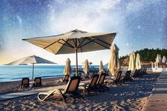 Scenic view of sandy beach on the beach with sun beds and umbrellas open against the sea and night sky. Fantastic starry Royalty Free Stock Photography