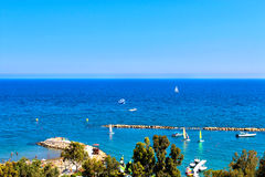 Scenic view of sandy beach with a pier with yachts and boats Royalty Free Stock Photography
