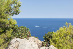 Sailing Boat in the Balearic Sea. Beautiful seaview from the top of the rocky mountain in Cap De Formentor, Mallorca. Little boat sailing in the Balearic sea Stock Photos