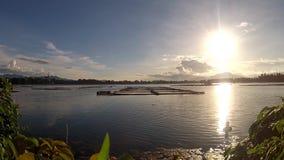 Scenic view of setting sun beneath mountain lake. Tracking shot stock footage