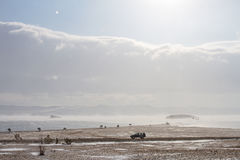 Scenic view on the shore of Lake Baikal in the winter and a black car rides along the rocky coast. Scenic view on the shore of Lake Baikal in the winter during Stock Images