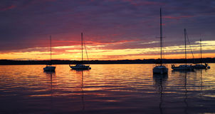 Scenic view of silhouetted yachts against colorful after sunset. Amazing summer evening landscape with group of drifting yachts on a lake during spectacular Royalty Free Stock Photo