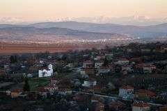 Scenic view of Slavyani village church with Lovech city in the background. Balkan mountain range in Bulgaria, evening light.  royalty free stock photography