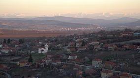 Scenic view of Slavyani village church with Lovech city in the background. Balkan mountain range in Bulgaria, evening light.  stock video footage