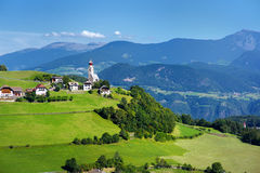 Scenic view of small Alpine village located in South Tyrol, Renon/Ritten region, Italy. Beautiful rocky mountain range on a background royalty free stock images