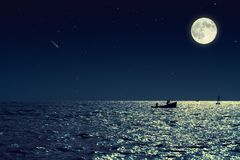Scenic view of small fishing boat in calm sea water at night and. Full moon Stock Photography
